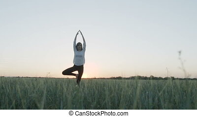 Yoga vrikshasana tree pose by woman at sunset - Yoga...