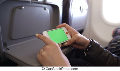 Woman Hand using cell phone in Airplane