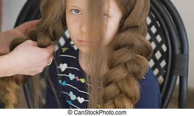 unhappy little girl. Mom or barber braids her braids. Brown...