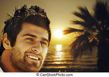 man on the sunset beach - young happy Turkish man on the...