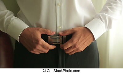 Close-up of a groom adjusts belt on his trousers....