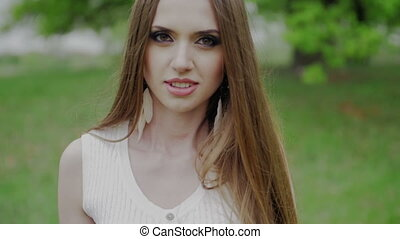 Beautiful woman with green eyes and brown hair goes to the camera slow motion