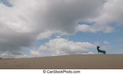 Beauty Girl in green dress running on sand dune while wind...