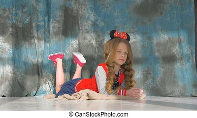 Little girl with long braids in a red jacket. Posing in the studio,