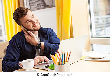 Handsome young guy is using a telephone - Attractive man is...