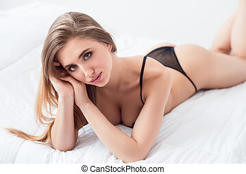 Sexually attractive girl lying in bed - Seductive glance...