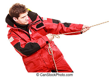 Young man pulling rope Male in waterproof coat Adventure...