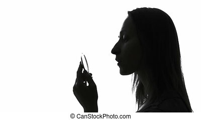 Woman applying lipstick - Silhouette of a woman applying...