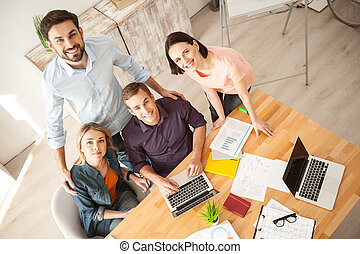 Cute four workers are expressing positive emotions - We are...