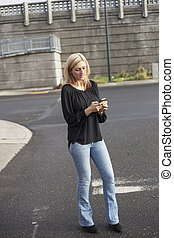 Woman in Black Top Texting on Cell Phone - Photo of a very...