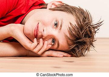 Close up on head of happy boy lying on floor - Sideways...