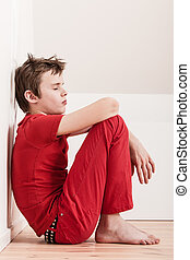 Withdrawn tired boy in red pants and shirt - Side profile...