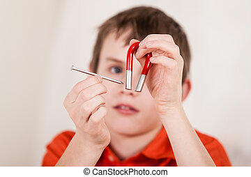 Close up on boy playing with nail and magnet - Selective...