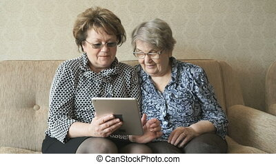 Two elderly women watch pictures using a tablet - Two...