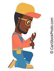 Repairman holding spanner - An african-american repairman...