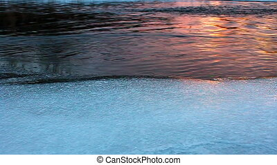 Winter River Sunset - Rays of sunlight reflect off chilly...