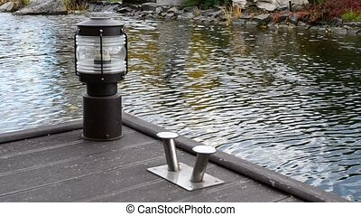 Moorage with stainless steel bollard and lantern on wooden deck
