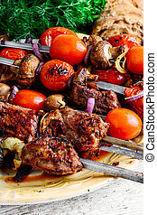Beef on skewers - few of the skewers with cooked meats and...