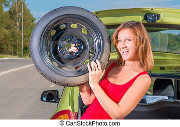 cheerful girl with a spare wheel near the car
