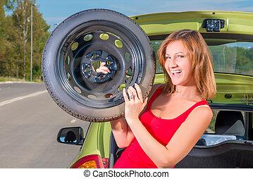 cheerful girl with a spare wheel near the car