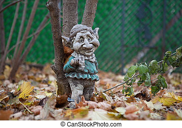 Weathered Garden Gnome resting against a tree