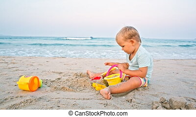 toddler boy plays sand toys beach - toddler boy plays sand...