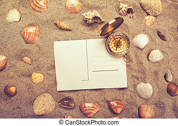 Blank postcard in hot beach sand and compass