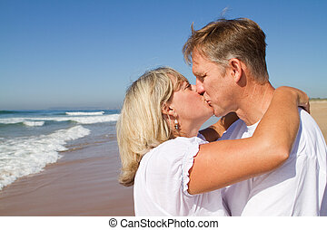 couple kissing - a middle-aged attractive couple kissing on...