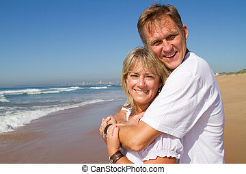 romantic beach couple - a romantic beach couple hugging and...