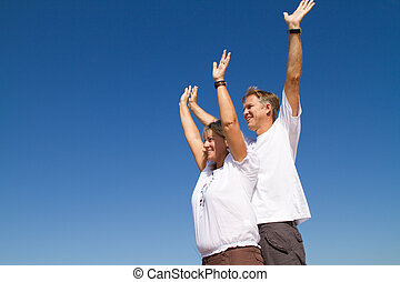 couple with arms stretched high - a middle-age couple with...