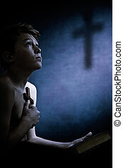 Religious young boy clasping a cross to his chest looking up...