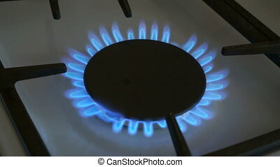 One gas burners burn blue flame on a gas stove