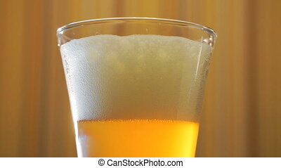 Jet of light beer fills in a beer mug on the table