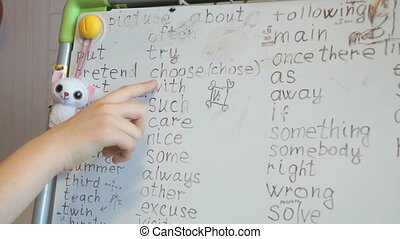 Finger of girl points English words on the board