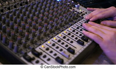 DJ works on the mixer at a nightclub