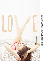 Girl on bed with her legs up forming the word love