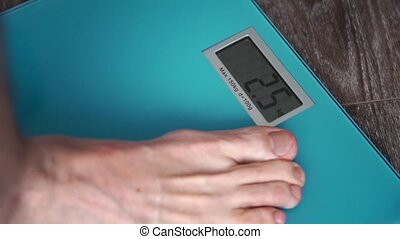 Men's feet on weight scale - Checking one's weight on a...