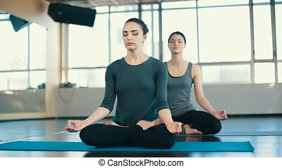 Young women meditating indoors - Two Young women do yoga...