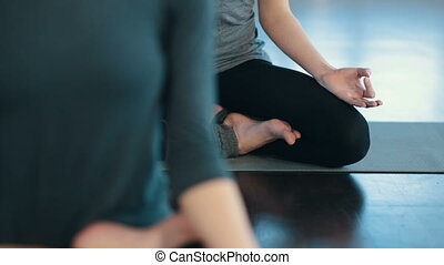 Young women meditating indoors