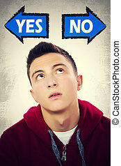 Teenage boy thinking what to choose between YES and NO -...