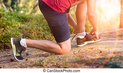 Young male runner tying his shoe laces
