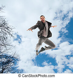 Jumping - Young man in business clothes jumping in the air
