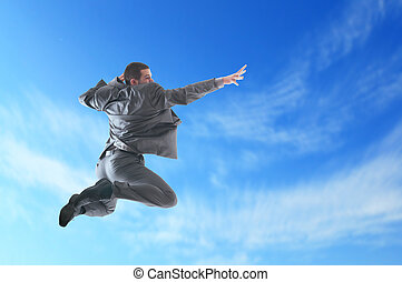 Jumping - Young business man jumping against blue sky