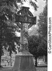 Large cross in a foggy old cemetery - Large statue of a...