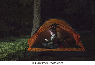 Man watching his smartphone in a tent.