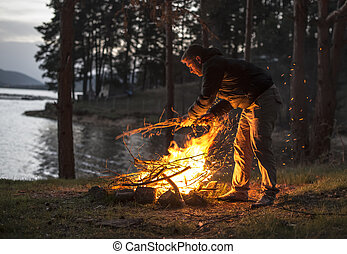 Man lights a fire in the fireplace in nature at night.