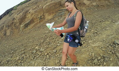 Girl tourist with map in mountains - Tourist girl unfolds...