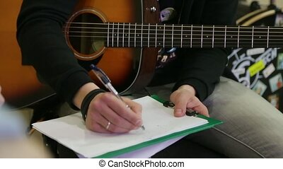 Guy with an acoustic guitar writes chords on a sheet