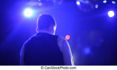 Host of the show standing on a brightly lit stage rear view