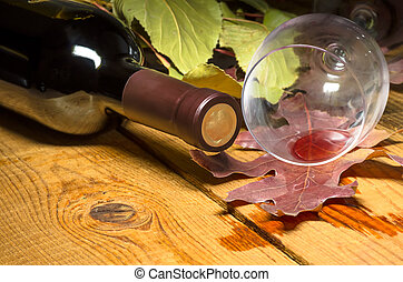 Red wine spilled from a glass on a wooden table on which the...